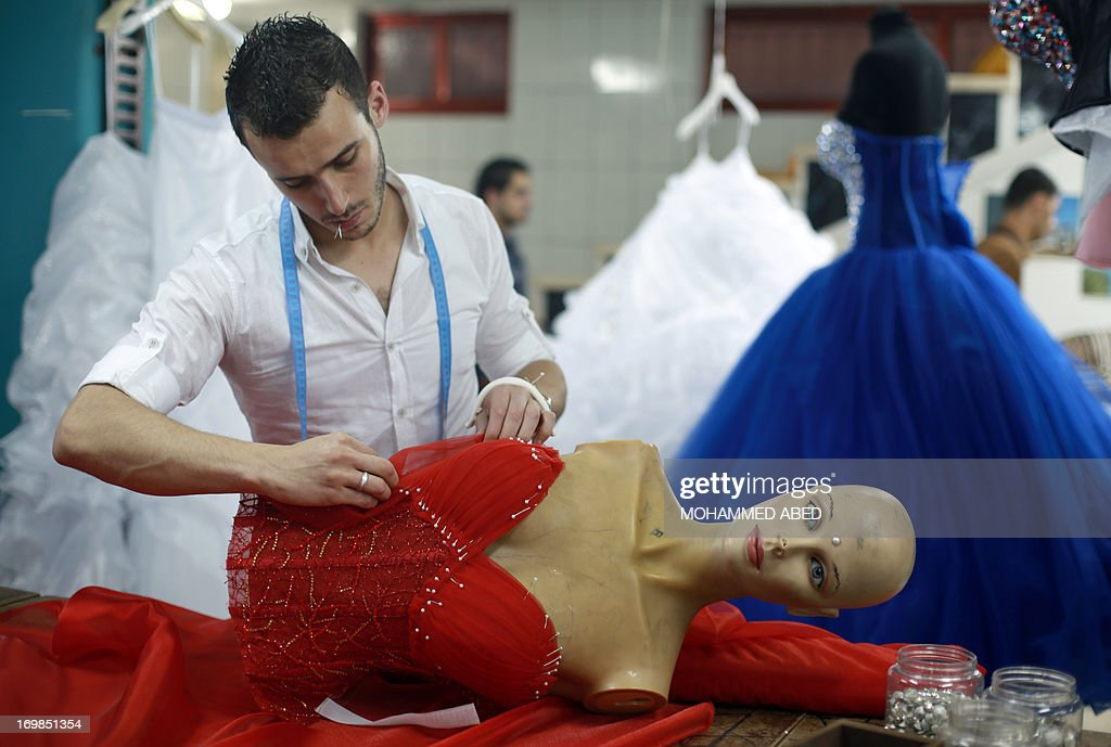 A Palestinian designer from the al-Ashi family pins the bodice to a gown at their atelier in Gaza City on June 3, 2013. The family started their own clothing line -wedding dresses and evening gowns- due to the difficulties and cost of smuggling and importing items into the Gaza Strip, either through legitimate crossings controlled by Israel to the north and east and Egypt in the south, or through smuggling tunnels dug under their southern border with Egypt and when the Egyptian border is closed.