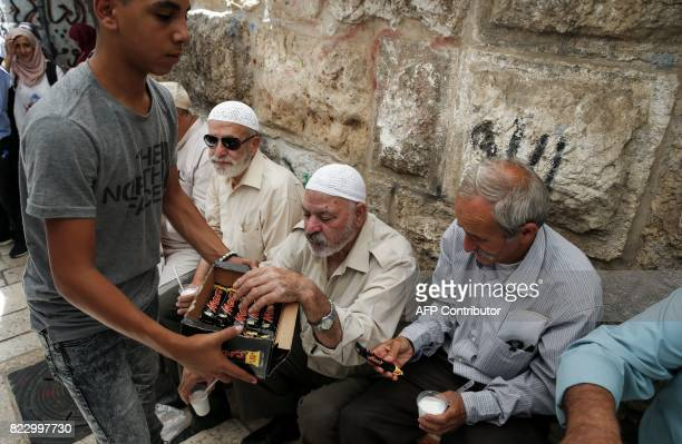 A Palestinian distributes chocolate bars donated to support demonstrators who have kept vigil for over a week as they pray outside AlAqsa mosque...
