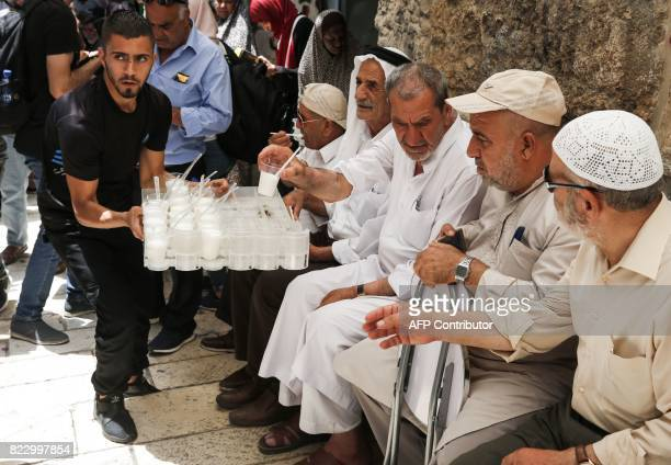 A Palestinian distributes drinks donated to support demonstrators who have kept vigil for over a week as they pray outside AlAqsa mosque compound...
