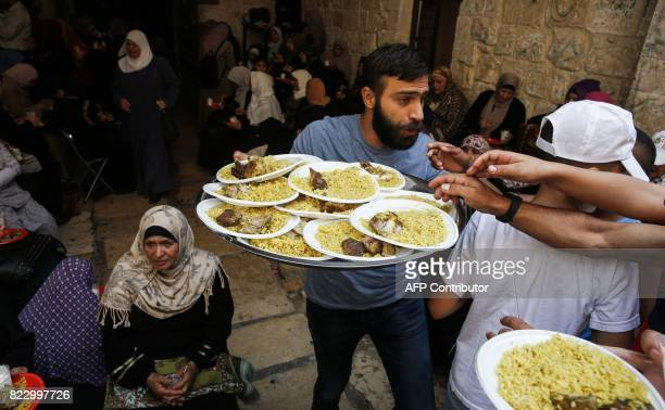 A Palestinian distributes food donated to support demonstrators who have kept vigil for over a week as they pray outside AlAqsa mosque compound also...