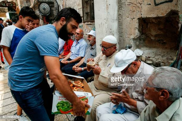 A Palestinian distributes pastries donated to support demonstrators who have kept vigil for over a week as they pray outside AlAqsa mosque compound...