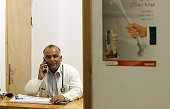 Palestinian doctor Ali Shroukh speaks on the phone in his consulting room at his private clinic on July 11 2016 in the southern West Bank village of...