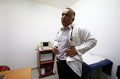 Palestinian doctor Ali Shroukh speaks on the phonestands in his consulting room at his private clinic on July 11 2016 in the southern West Bank...