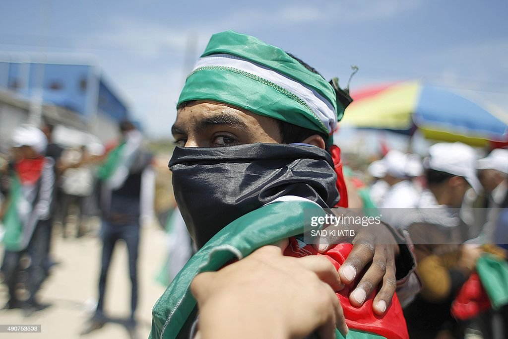 A Palestinian draped in the national flag gathers in Gaza City on May 15, 2014, to mark Nakba Day. Palestinians are marking 'Nakba day' which means in Arabic 'catastrophe' in reference to the birth of the state of Israel 66-years-ago in British-mandate Palestine, which led to the displacement of hundreds of thousands of Palestinians who either fled or were driven out of their homes during the 1948 war over Israel's creation. AFP PHOTO/ SAID KHATIB