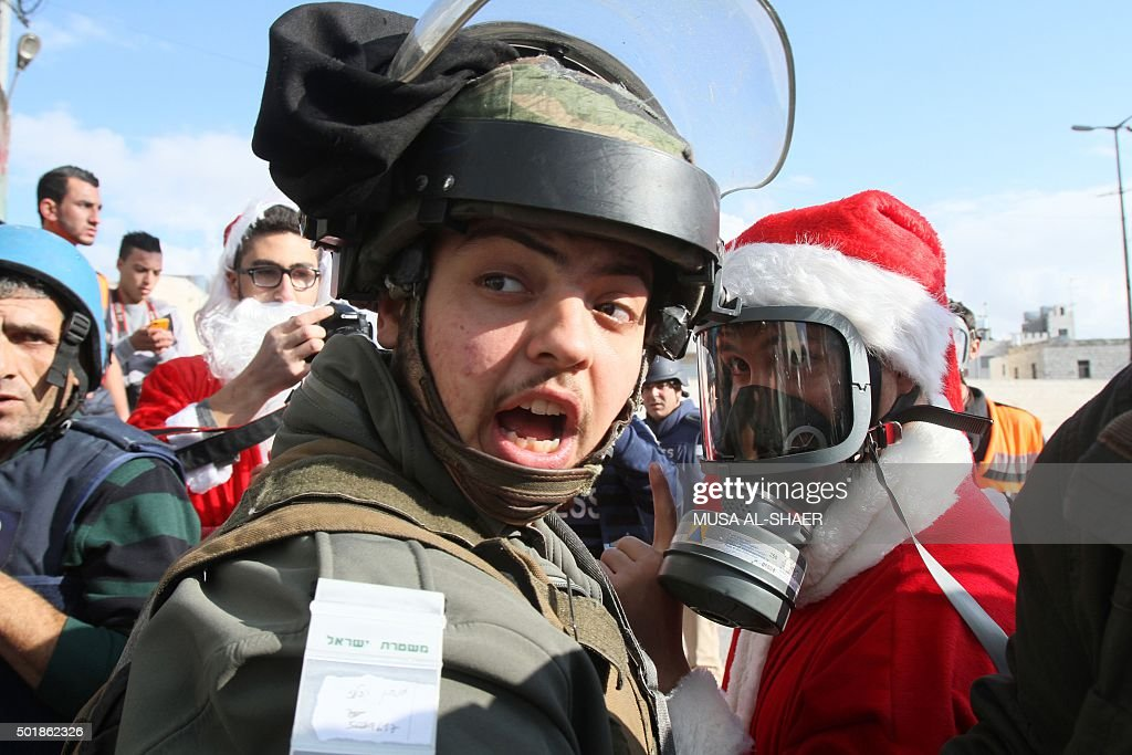 Palestinian dressed up as Santa Claus talks to an Israeli soldier during a demonstration in front of a gate along the Israeli controversial...