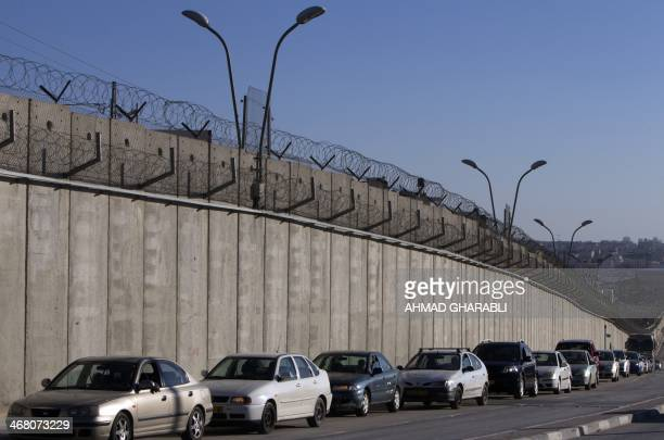 Palestinian drivers wait in their cars next to Israel's controversial separation barrier ahead of crossing throught the Qalandia checkpoint after...