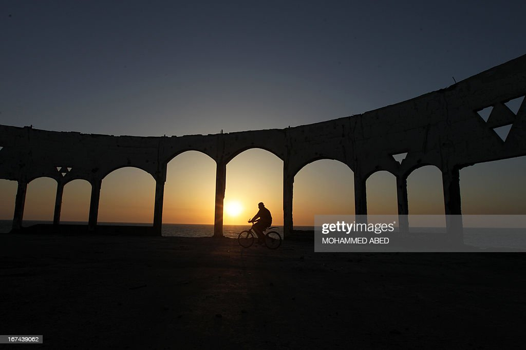 A Palestinian drives his bicycle past archs at sunset on April 25, 2013 on Beit Lahia beach, northern of Gaza Strip.