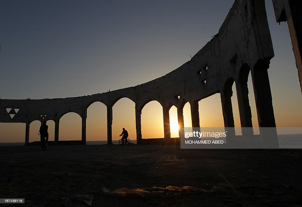 A Palestinian drives his bicycle past archs at sunset on April 25, 2013 on Beit Lahia beach, northern of Gaza Strip. AFP PHOTO/MOHAMMED ABED