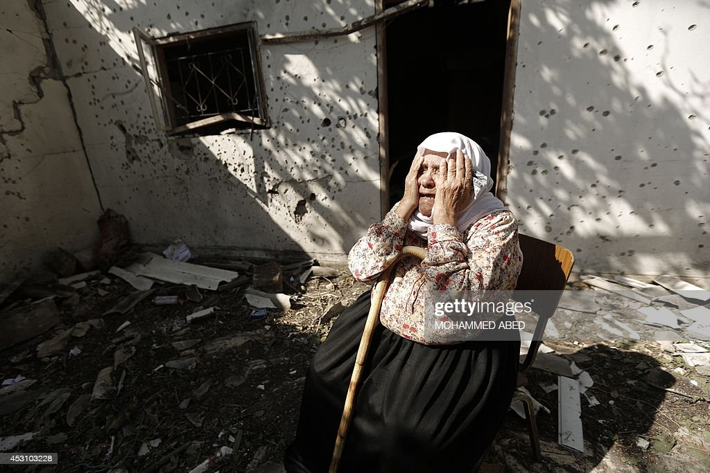 A Palestinian elderly woman sits crying after an Israeli military strike hit a house killing at least three members of the Wahdan family on August 3...