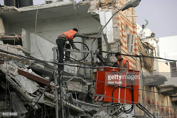 Palestinian electricians make repairs to the electricity network after it was damaged during an Israeli airstrike on January 16 in the Gaza Strip...