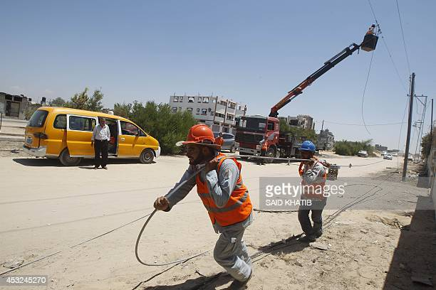 Palestinian electricity company workers inspect power lines destroyed following an earlier Israeli air strike in Rafah in the southern Gaza Strip on...