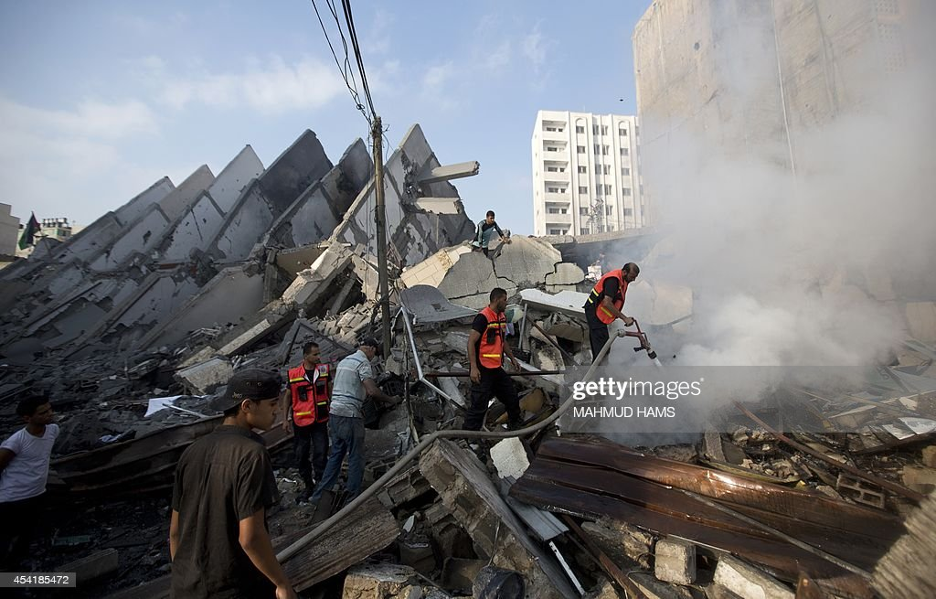 Palestinian emergency services extinguish smoke in the remains of a building that was destroyed by an Israeli air strike in Gaza City on August 26, 2014, killing two Palestinians, as Israel pursued its campaign to stop rocket fire by Hamas militants from the enclave, medics said. Egypt has proposed a new ceasefire in the Gaza conflict that would open key border crossings into the battered Palestinian territory, after Israeli raids killed at least 10 more Palestinians.