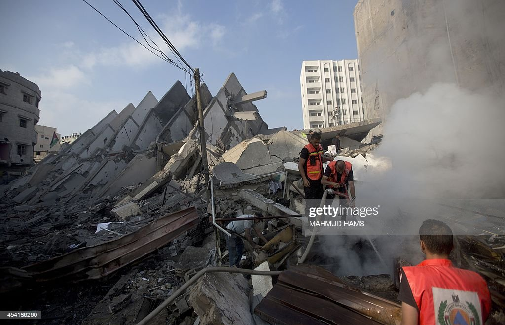 Palestinian emergency services extinguish smoke in the rubble of a building that was destroyed by an Israeli air strike in Gaza City on August 26, 2014, killing two Palestinians, as Israel pursued its campaign to stop rocket fire by Hamas militants from the enclave, medics said. Egypt has proposed a new ceasefire in the Gaza conflict that would open key border crossings into the battered Palestinian territory, after Israeli raids killed at least 10 more Palestinians.