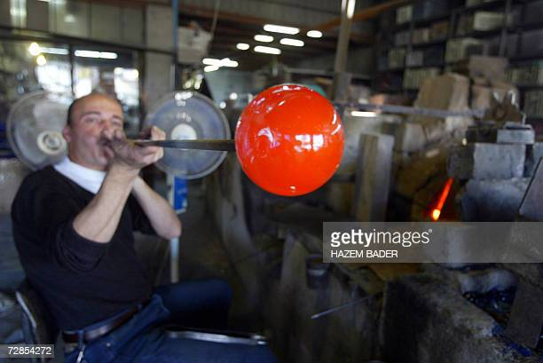 Palestinian employee at the alNatsheh glass factory blow red hot molten glass into a ball as he makes Christmas baubles and bells 20 December 2006 in...