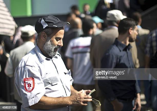 A Palestinian employee of the former Hamas government counts his money outside a post office in Gaza City on October 29 2014 after receiving 1200 US...