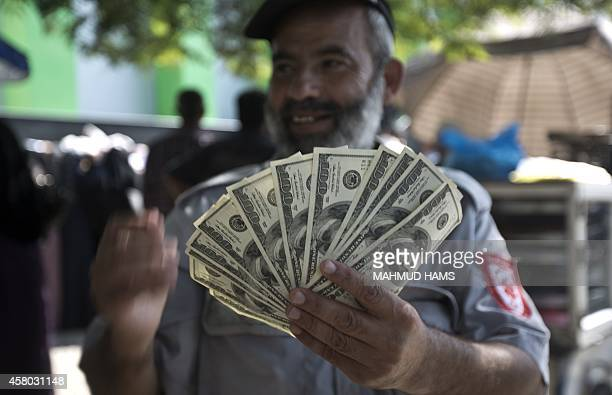 A Palestinian employee of the former Hamas government holds 1200 US dollars in cash outside a post office in Gaza City on October 29 2014 after...