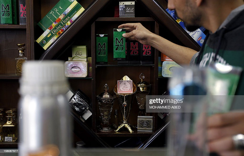 A Palestinian employee of the 'Stay Stylish' shop displays packaged M75 perfume bottles in Gaza City on December 10, 2012. 'Victory' has never smelled so sweet -- or at least that's what they would have you believe at the shop selling Gaza's newest fragrance named M75 after a long-range Hamas rocket. AFP PHOTO/MOHAMMED ABED