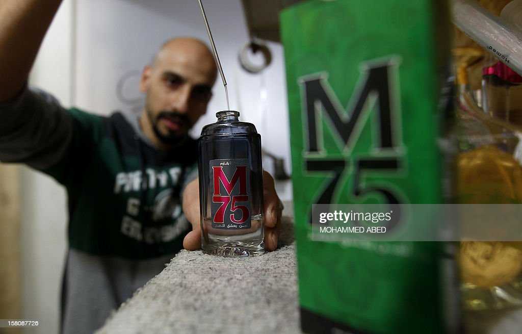 A Palestinian employee of the 'Stay Stylish' shop fills an M75 perfume bottle in Gaza City on December 10, 2012. 'Victory' has never smelled so sweet -- or at least that's what they would have you believe at the shop selling Gaza's newest fragrance named M75 after a long-range Hamas rocket. AFP PHOTO/MOHAMMED ABED