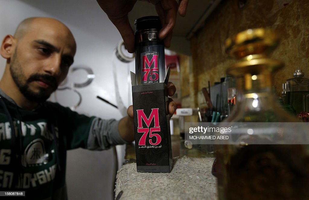 A Palestinian employee of the 'Stay Stylish' shop shows an M75 perfume bottle in Gaza City on December 10, 2012. 'Victory' has never smelled so sweet -- or at least that's what they would have you believe at the shop selling Gaza's newest fragrance named M75 after a long-range Hamas rocket. AFP PHOTO/MOHAMMED ABED