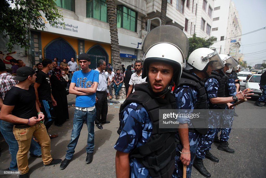 A Palestinian employee paid by Palestinian Authority stands next to a policeman as he waits to receive his salary outside a closed bank in Gaza City...