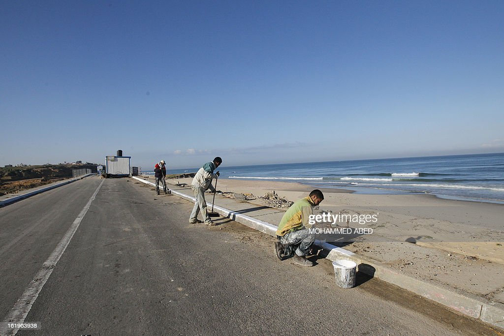 Palestinian employees do the final work on a road leading to a bridge which was destroyed during Israel's last military assault on the Gaza Strip, on February 18, 2013 in Gaza City.