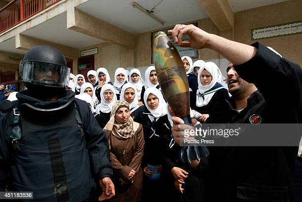 Palestinian explosives expert loyal to the ruling Hamas movement holds a mortar shell as he explains to schoolgirls the dangers of unexploded...