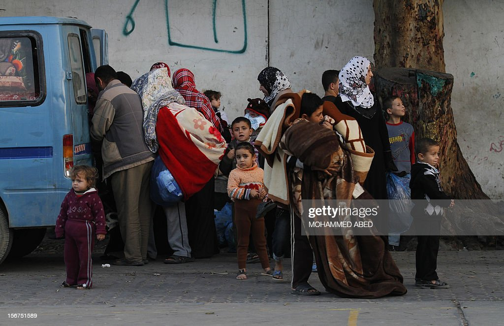 Palestinian families load their belongings into a vehicle after they evacuated their homes to take shelter at a United Nations (UN) school in Gaza City on November 20, 2012. A group of 38 aid agencies urged the international community to take action to secure a ceasefire in Gaza to prevent 'another widespread humanitarian disaster.'
