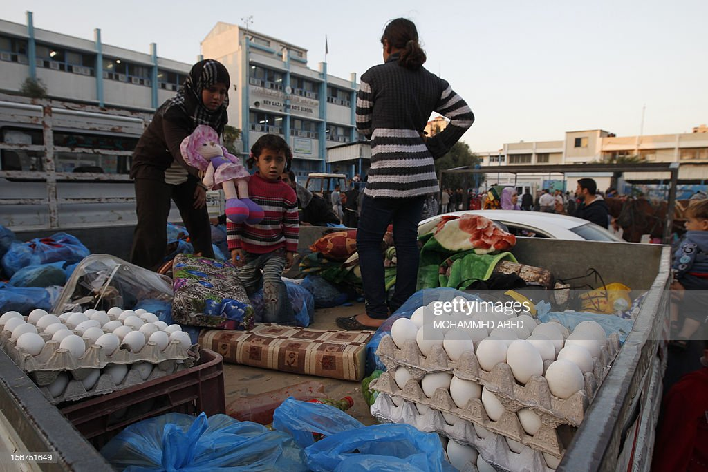 Palestinian families load their belongings into a vehicle as they evacuate their homes to take shelter at a United Nations (UN) school in Gaza City on November 20, 2012. A group of 38 aid agencies urged the international community to take action to secure a ceasefire in Gaza to prevent 'another widespread humanitarian disaster.'