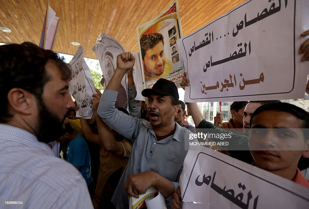 Palestinian families of those killed in violence in the Gaza Strip, hold posters reading in Arabic: 'punishment for criminals' as they protest in support of execution outside a conference being held by non-governmental organisations on the occasion of the World Day Against the Death Penalty, in Gaza City, on October 9, 2013. The Gaza Strip's Islamist rulers Hamas hanged a prisoner today who had been convicted of murder, its interior ministry said, despite international calls for a halt to executions. Under Palestinian law, collaboration with Israel, murder and drug trafficking are all punishable by death. AFP PHOTO/MOHAMMED ABED