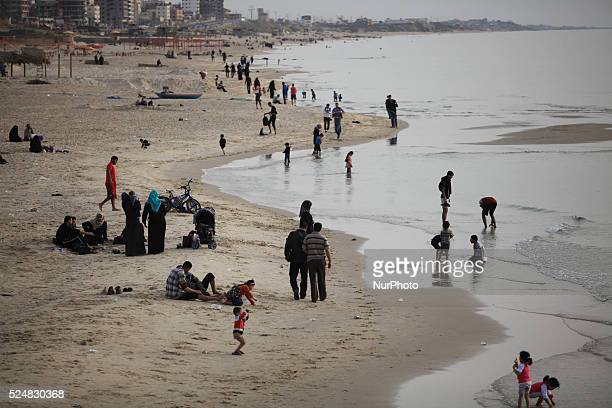 Palestinian families swim and palestinian youth jumps into the Mediterranean Sea as he enjoys a warm day on April 21 2015 at the seaport in Gaza City
