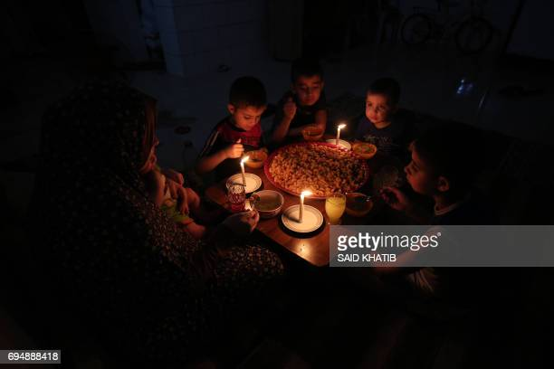 A palestinian family eats dinner by candlelight at their makeshift home in the Rafah refugee camp in the southern Gaza Strip during a power outage on...