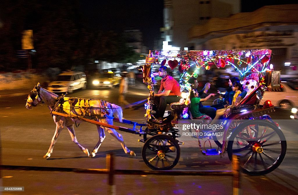 A Palestinian family enjoys a ride on a horse cart near a park in downtown Gaza City on August 28, 2014 one day after an unconditional ceasefire was signed between Hamas and Israel. Millions in and around the war-torn coastal enclave were enjoying a second day of peace after the guns fell silent.
