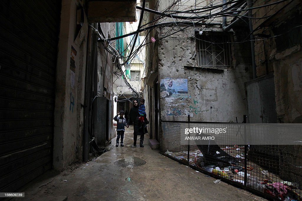 Palestinian family from the Syrian refugee camp of Yarmuk walks through the Shatila refugee camp in the Lebanese capital Beirut on December 19, 2012. Some 13,000 members of Syria's Palestinian refugee community have gone back to square one in neighbouring Lebanon. Like their ancestors, they too have been forced to flee their birthplace into exile.
