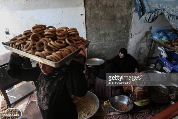 Palestinian family make traditional datefilled cookies in preparation for the Eid alFitr holiday at their home in Rafah in the southern Gaza Strip on...