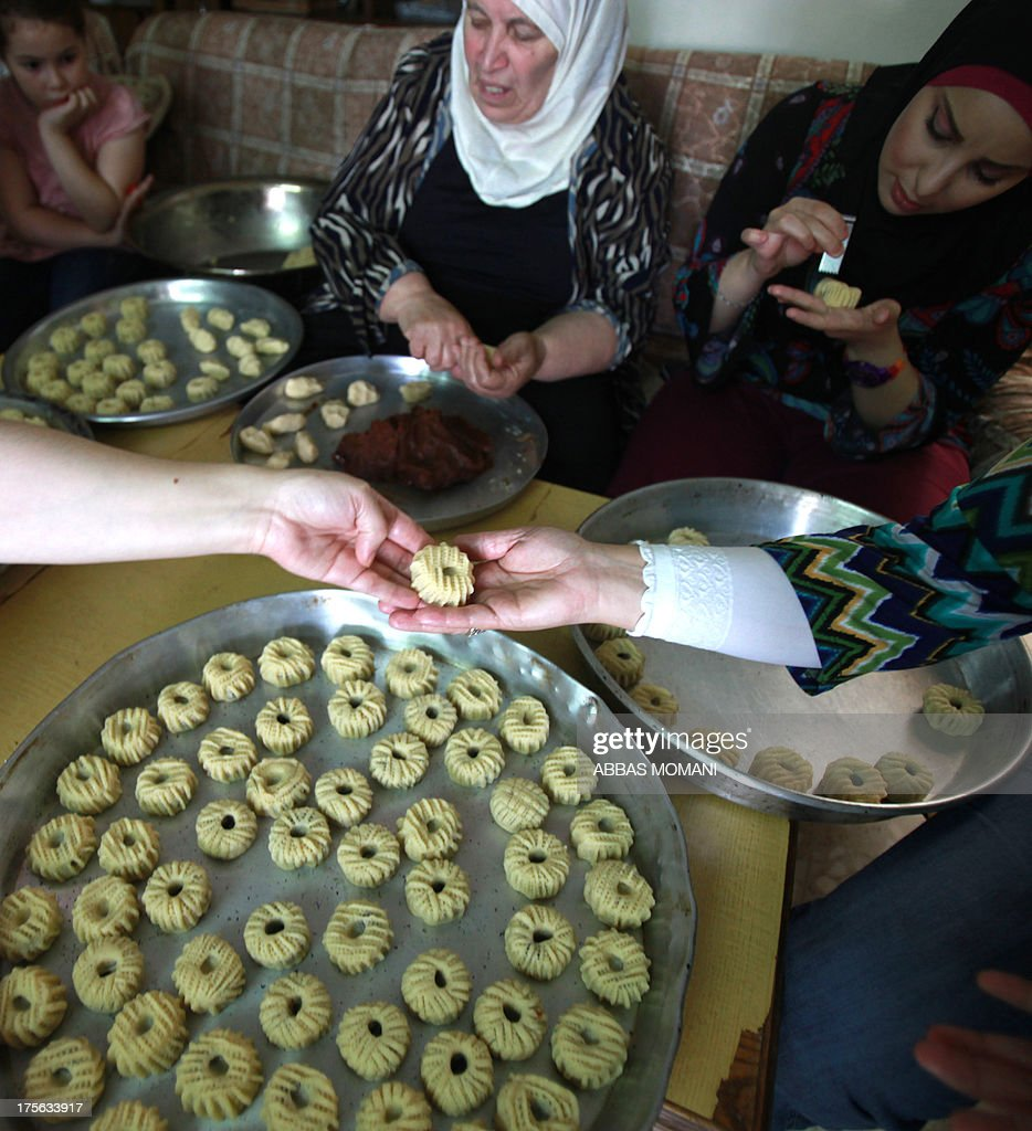 A Palestinian family prepare traditional biscuits popular on the occasion of Eid al-Fitr at their house in the West Bank city of Ramallah, on August 5, 2013. Muslims around the world are preparing to celebrate the Eid al-Fitr holiday, which marks the end of the fasting month of Ramadan. Preparations include buying new clothes, toys and special sweets.