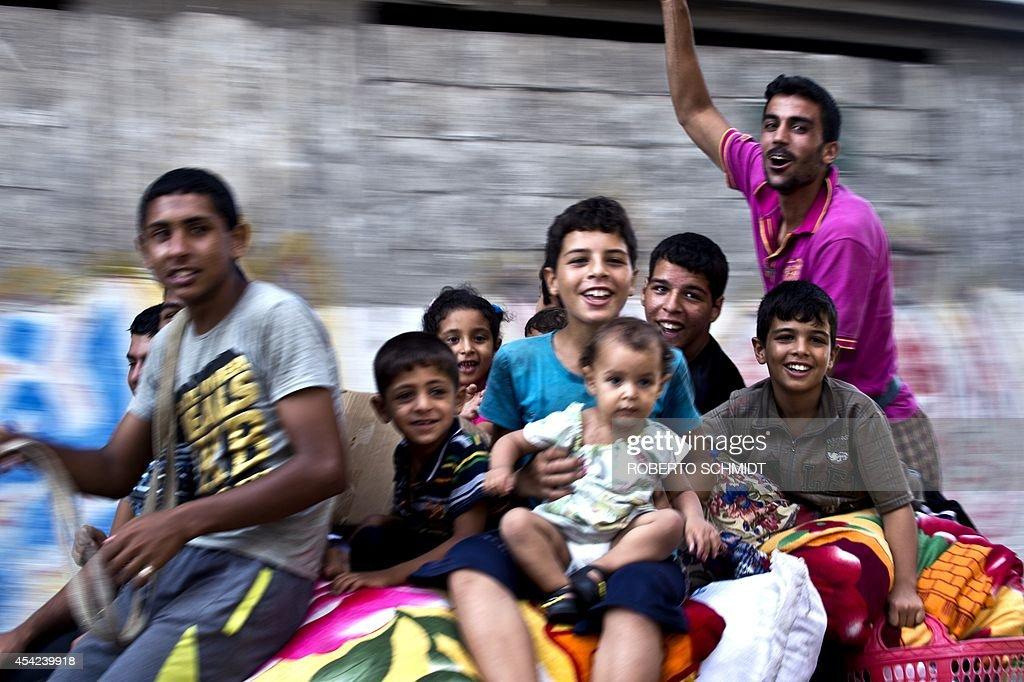 A Palestinian family ride on top of a horse cart as they head home with their belongings in the Shejaiya neighborhood on August 27 2014 The Shejaiya...