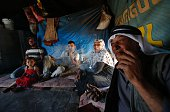 A Palestinian family sit inside their tent in the Palestinian village of Khirbet Zanuta located in the hills south of the West Bank city of Hebron on...