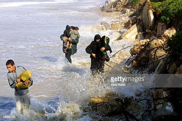 Palestinian family walks along a flooded dirt road located on a beach in order to avoid an Israeli army blockade set up near the Netzarim Jewish...