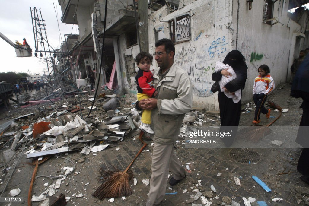 A Palestinian family walks near debris of destroyed buildings following Israeli air strikes in Rafah, southern Gaza Strip on January 1, 2008. Israel launched the New Year with fresh air strikes on Gaza that took the death toll from its blitz on Hamas to 400 as international efforts to secure a truce foundered.