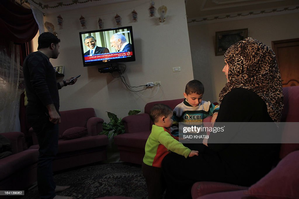 A Palestinian family watch a televised press conference for US President Barack Obama and Israeli President Shimon Peres, at their home in the southern Gaza Strip town of Rafah on March 20, 2013. Obama arrived in Israel for the first time as president, vowing an 'eternal' alliance with the Jewish state as it faces Iran's nuclear threat and perilous change in the Middle East. AFP PHOTO/ SAID KHATIB