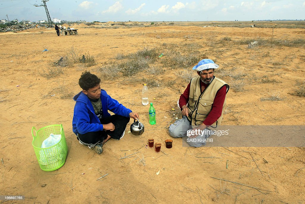 A Palestinian farmer and his son have a cup of tea after working in their field in Absan near the border between Israel and the Gaza Strip on November 24, 2012, on three days after a truce was declared between Israel and Hamas. Israel slammed Palestinian president Mahmud Abbas for his support for Gaza following its confrontation with the Jewish state, while casting aspersions on the legitimacy of his upcoming UN statehood bid. AFP PHOTO/SAID KHATIB