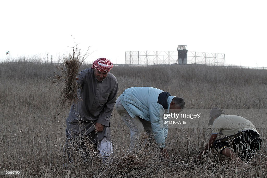 Palestinian farmer Ibrahim al-Qarah (L), 63, works in his field in Absan near the border (behind) between Israel and the Gaza Strip on November 24, 2012, on three days after a truce was declared between Israel and Hamas. Israel slammed Palestinian president Mahmud Abbas for his support for Gaza following its confrontation with the Jewish state, while casting aspersions on the legitimacy of his upcoming UN statehood bid.