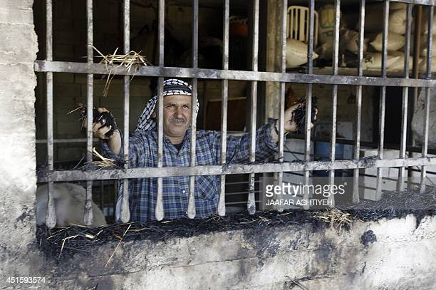 A Palestinian farmer inspects his vandalized property allegedly burnt by Jewish settlers in the village of Aqraba in the Israeli occupied Palestinian...