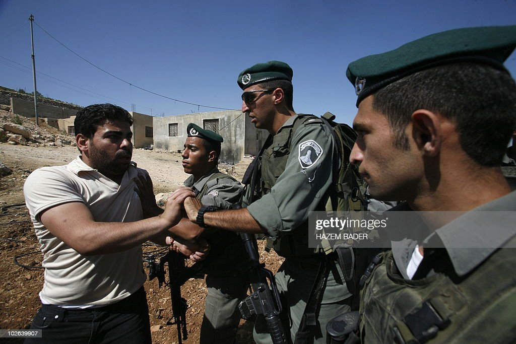 A Palestinian farmer, whose agriculture land was partially destroyed by the army, is pushed away by an Israeli border policeman as he tries to protest on July 6, 2010 in the West Bank city of Hebron across the road from the Israeli settlement of Kiryat Arba. AFP PHOTO / HAZEM BADER
