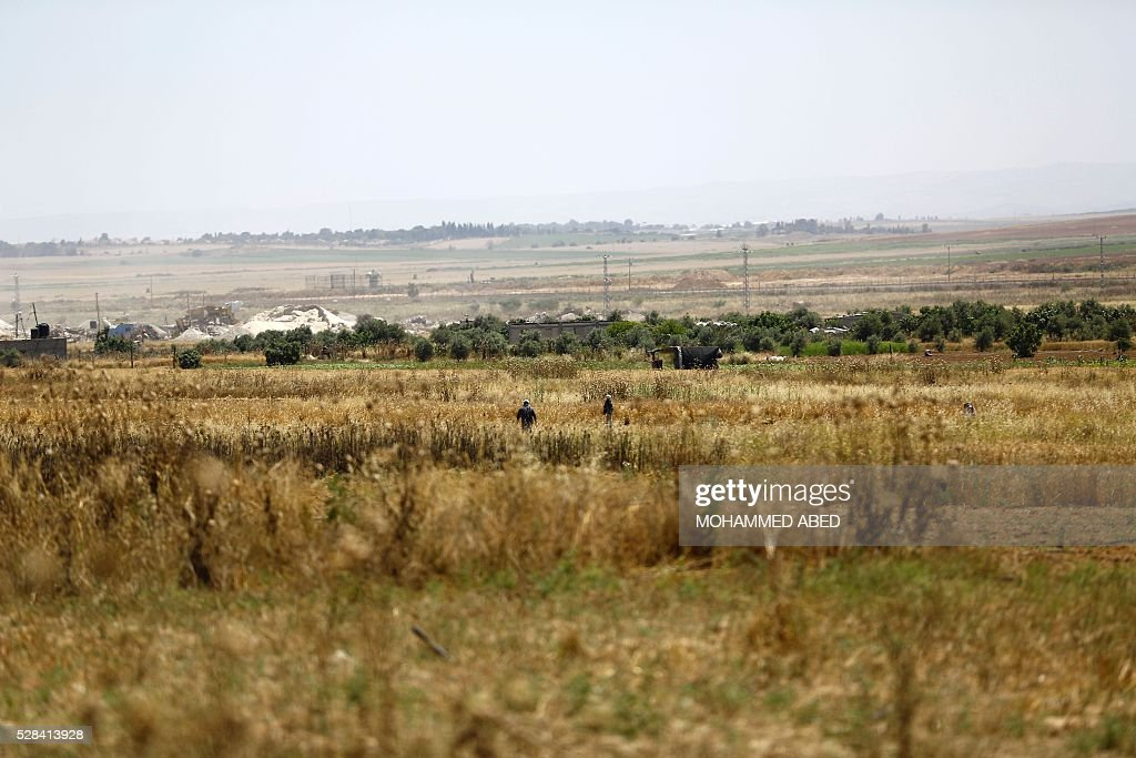 Palestinian farmers work in a field near the border with Israel east of Gaza City, on May 5, 2016. Israeli forces uncovered a Hamas tunnel stretching across the border, the Israeli army said, the second such discovery in recent weeks. Army spokesman Peter Lerner said the tunnel was 28-29 metres deep and stretched into Israeli territory, though he did not say how far. ABED