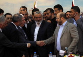 Palestinian Fatah delegation chief Azzam alAhmed shakes hands with Hamas deputy leader Musa Abu Marzuk in the presence of Hamas prime minister in the...