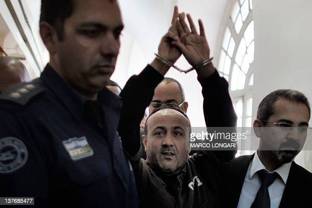 Palestinian Fatah leader Marwan Barghuti is escorted in handcuffs by Israeli police into Jerusalem's Magistrate Court to testify as part of a US...