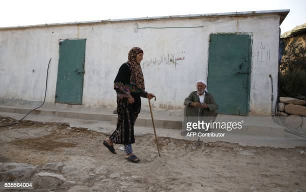 Palestinian Fatima walks past her husband Yousof alAdraa as he sits outside their home in the village of Jinba south of the West Bank city of Hebron...