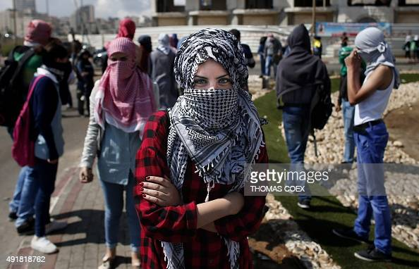 A Palestinian female demonstrater poses for the camera ahead of clashes with Israeli security forces in Beit El near the West Bank city of Ramallah...