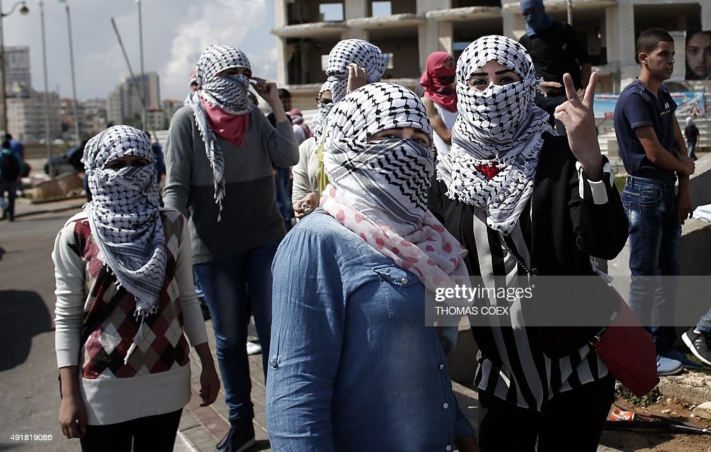 Palestinian female demonstraters pose for the camera ahead of clashes with Israeli security forces in Beit El near the West Bank city of Ramallah on...